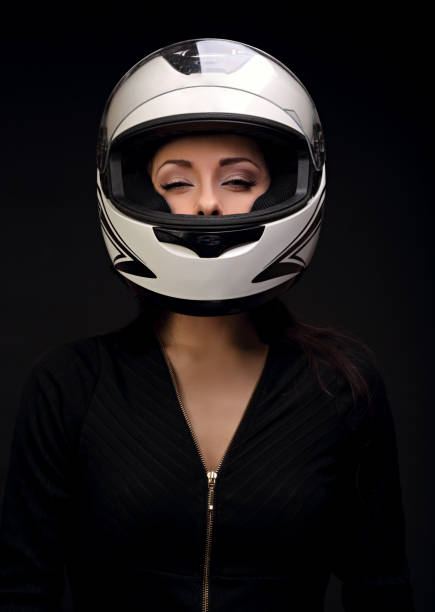 Beautiful sexy makeup woman looking in white motorcycle helmet on black background. Closeup dark portrait - foto stock