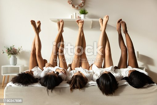 Beautiful sexy multiethnic girls best friends wear bathrobes lying on bed in row raise legs up celebrate bridal shower bachelorette spa party together, epilation depilation feet skin beauty concept