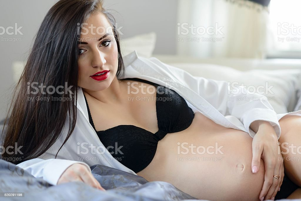 Beautiful sexy pregnant woman on bed - Stock image .