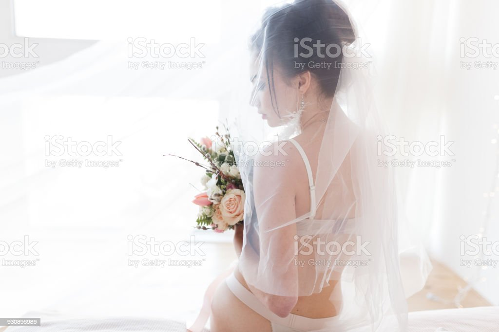 7b6c632d5d7 Beautiful sexy stylish young bride in lingerie with nice bouquet sitting on  bed under veil. Horizontal view with copy space - Stock image .