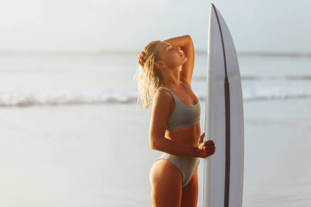 Beautiful sexy surfer girl on the beach at sunset stock photo