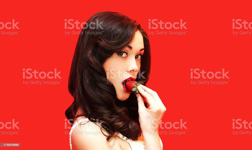 Beautiful sexy woman enjoying the taste of fresh strawberry stock photo
