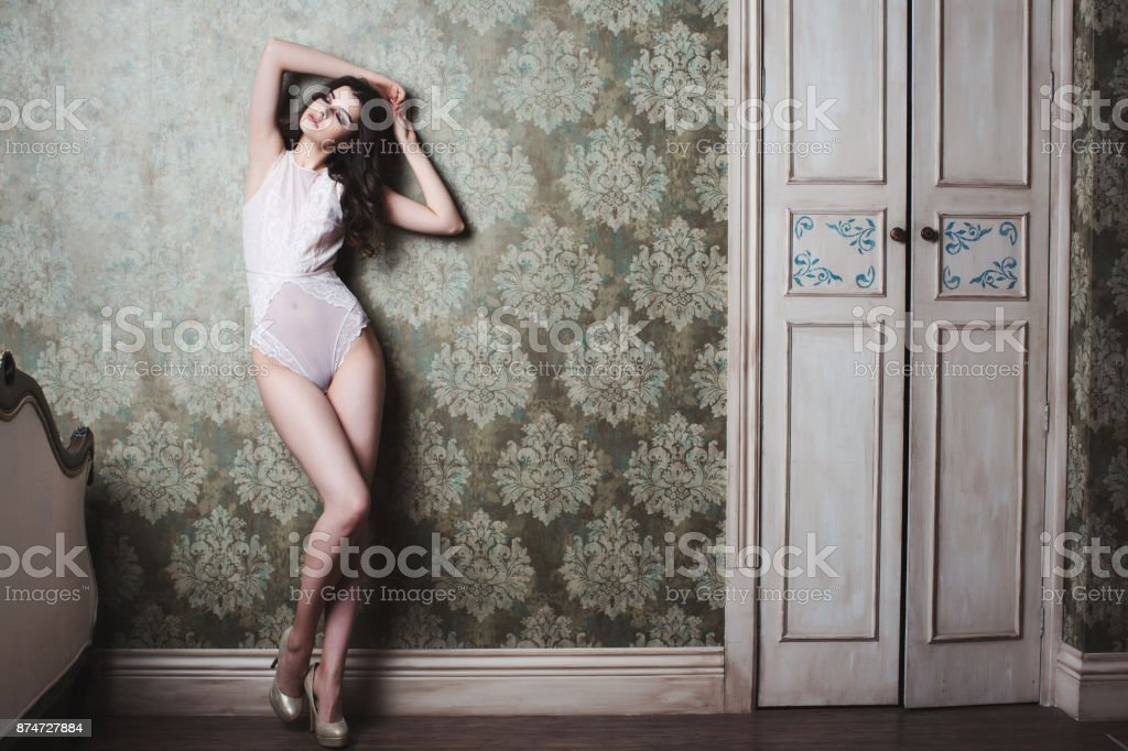 Beautiful sexy woman in lingerie posing in a vintage interior. stock photo