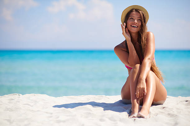 Beautiful sexy woman sitting on the beach over sea background stock photo