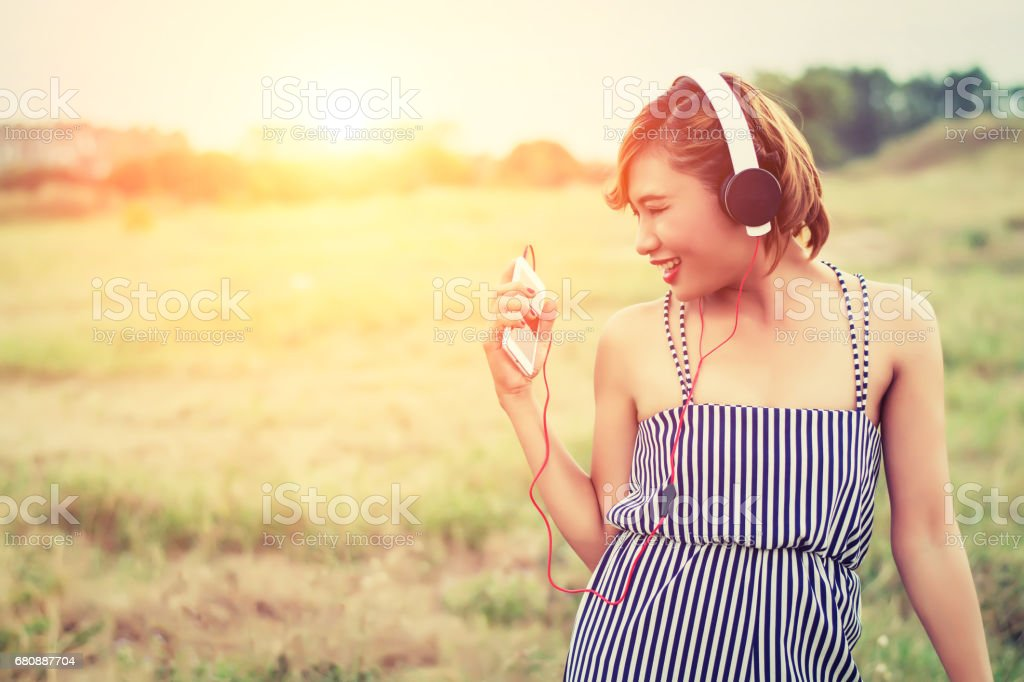 beautiful sexy woman with blue dress standing listening music in the flower fields smiley and enjoying music royalty-free stock photo