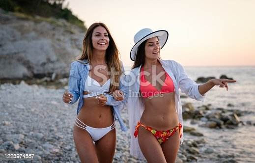 Beautiful sexy women, friend enjoying summer holiday, walking on the beach