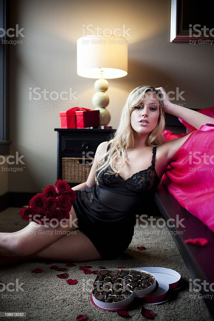 Beautiful Sexy Young Blond Woman in Black Lingerie, Roses, Chocolates stock photo