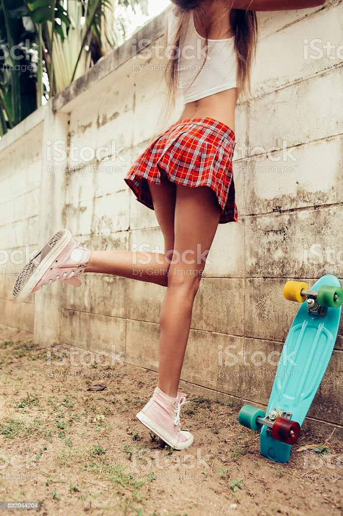 beautiful sexy young lady in mini skirt with skateboard stock photo