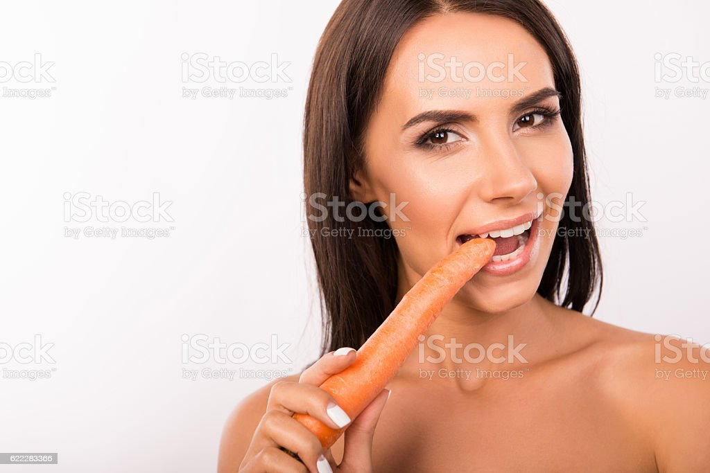 beautiful sexy young woman  eating  carrot stock photo