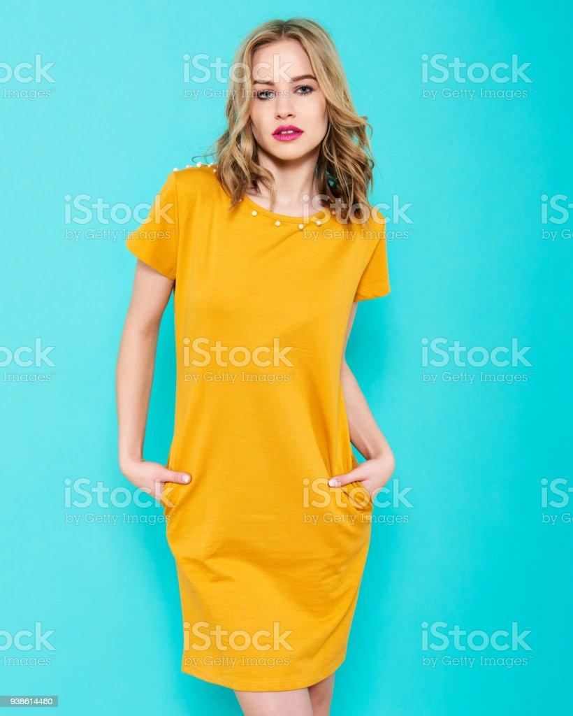 f08c6c6f8d8 Hermosa mujer joven sexy en retrato de estudio de vestido de fiesta  amarillo brillante sobre fondo