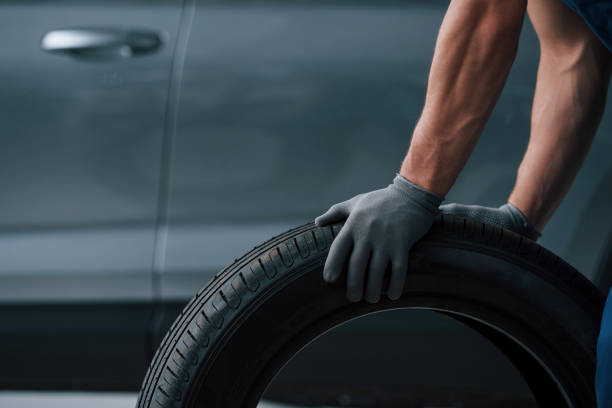 Beautiful shadows. Mechanic holding a tire at the repair garage. Replacement of winter and summer tires stock photo