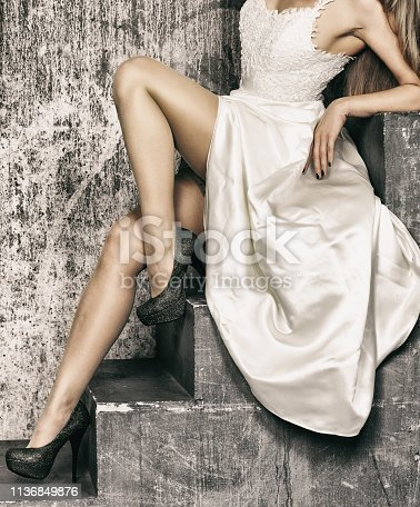 Beautiful shapely female legs with high heels on the stairs near the old wall
