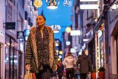 Beautiful shaven headed brunette black female tourist enjoying winter shopping in the high street