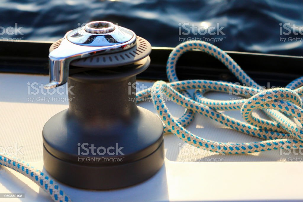 Beautiful shiny windlass on a board of a yacht or motor boat with a blue mooring cable rope on blue water background stock photo