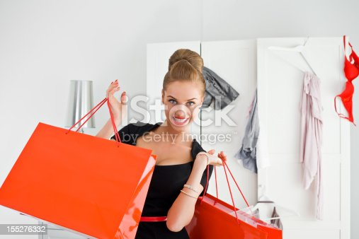 Portrait of excited young adult woman holding red shopping bags in both hands with messy wardrobe in the background. smiling at the camera.