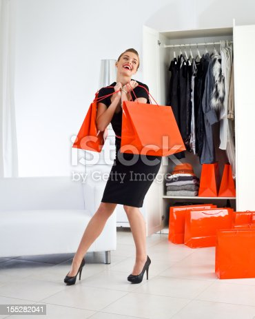 Portrait of happy young adult woman holding red shopping bag in her hand with wardrobe in the background.