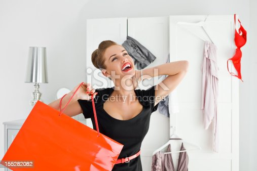 Portrait of happy young adult woman holding red shopping bag in her hand with messy wardrobe in the background.