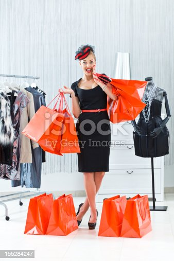 Elegant and happy young adult woman posing with many shopping bags in luxury boutique.
