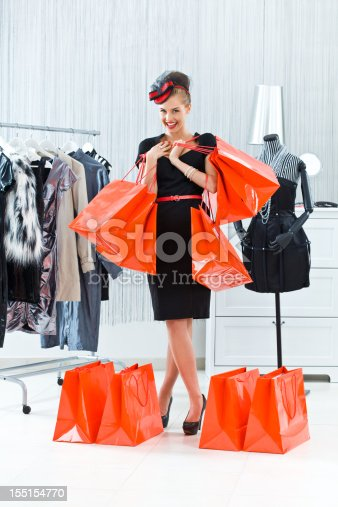 Portrait of excited and well-dressed young adult woman standing in boutique with many shopping bags, smiling at the camera.