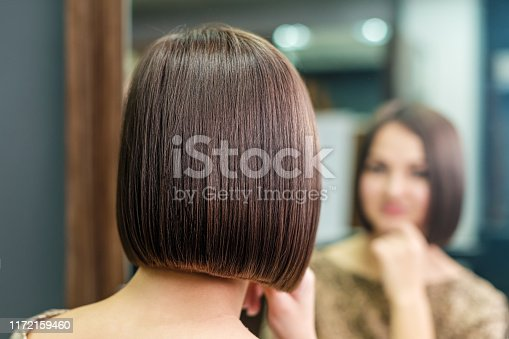 young woman is looking in the mirror with beautiful hairstyle in beauty salon, beauty concept
