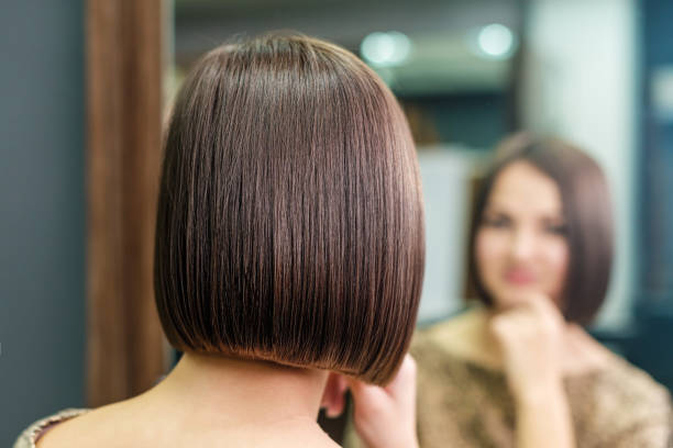 Beautiful short hairstyle of young woman young woman is looking in the mirror with beautiful hairstyle in beauty salon, beauty concept highlights hair stock pictures, royalty-free photos & images