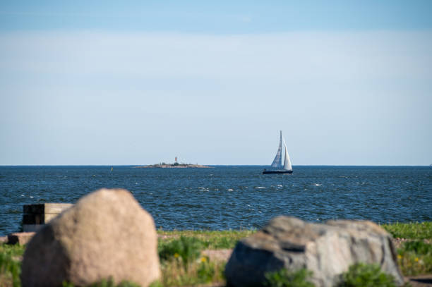 A beautiful shot from a waterfront towards the sea with blocks of granite in forefront and a sailboat sailing across the horizon stock photo