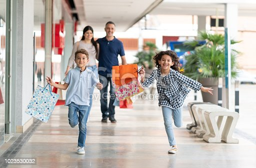 Beautiful siblings having fun at the mall running and holding shopping bags and parents walking behind them embracing each other