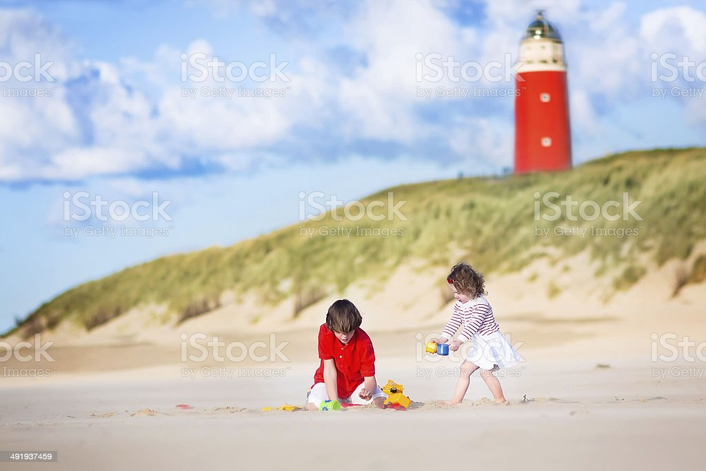 Beautiful siblings playing on sands beach next to lighthouse stock photo