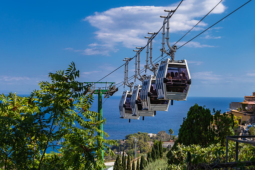 """Beautiful Sicilian landscape with cable cars """"funivia"""" that connect the historic center of Taormina with its beach area of Mazzaró and Mount Tauro."""