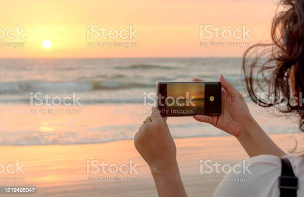 Photo of Beautiful side view photo of Young tourist girl exploring the world during vacations and is taking a sunset/sunrise shot in her smartphone. The photo to be clicked is visible in phone viewfinder.