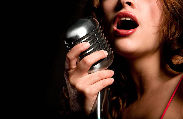 Beautiful singer singing with microphone stock photo