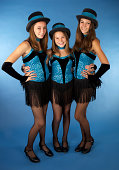 Three beautiful sisters- ages ten,thirteen and sixteen wearing their matching jazz dance costumes.  Shot in the studio on a blue background.