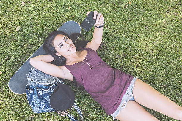 beautiful skater girl taking a selfie while lying on grass - philippines girl stock photos and pictures