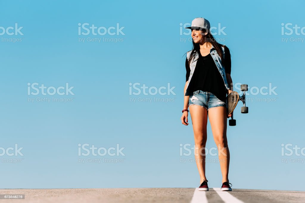 Beautiful skater woman posing with her longboard. royalty-free stock photo