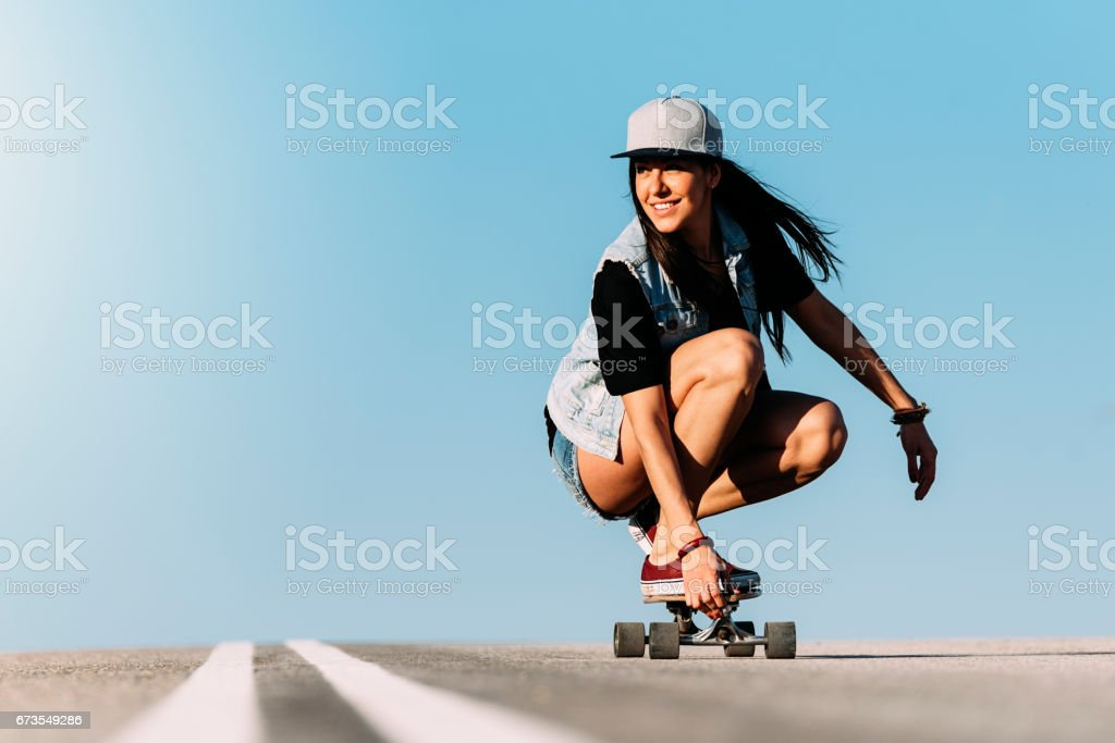 Beautiful skater woman riding on her longboard. royalty-free stock photo