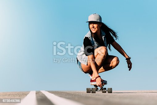 Beautiful young skater woman riding on her longboard in the city.Beautiful young skater woman riding on her longboard in the city.Beautiful young skater woman riding on her longboard in the city.Beautiful young skater woman riding on her longboard in the city.