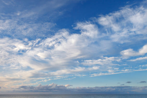 Beautiful sky over the sea with cirrus and small cumulus clouds stock photo
