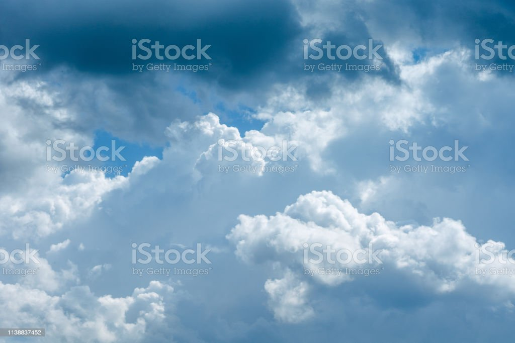 Beautiful blue and cloudy sky with white fluffy clouds in white and...