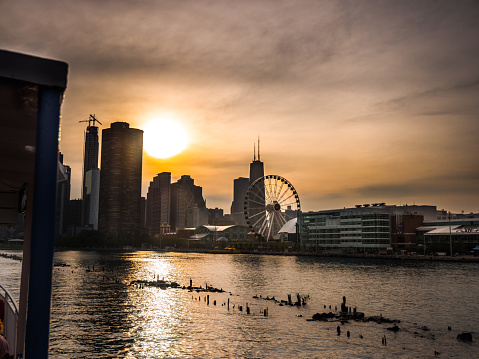 Beautiful skyline sunset view in Chicago with building silhouettes and sun reflecting in the water along the shore of Lake Michigan.