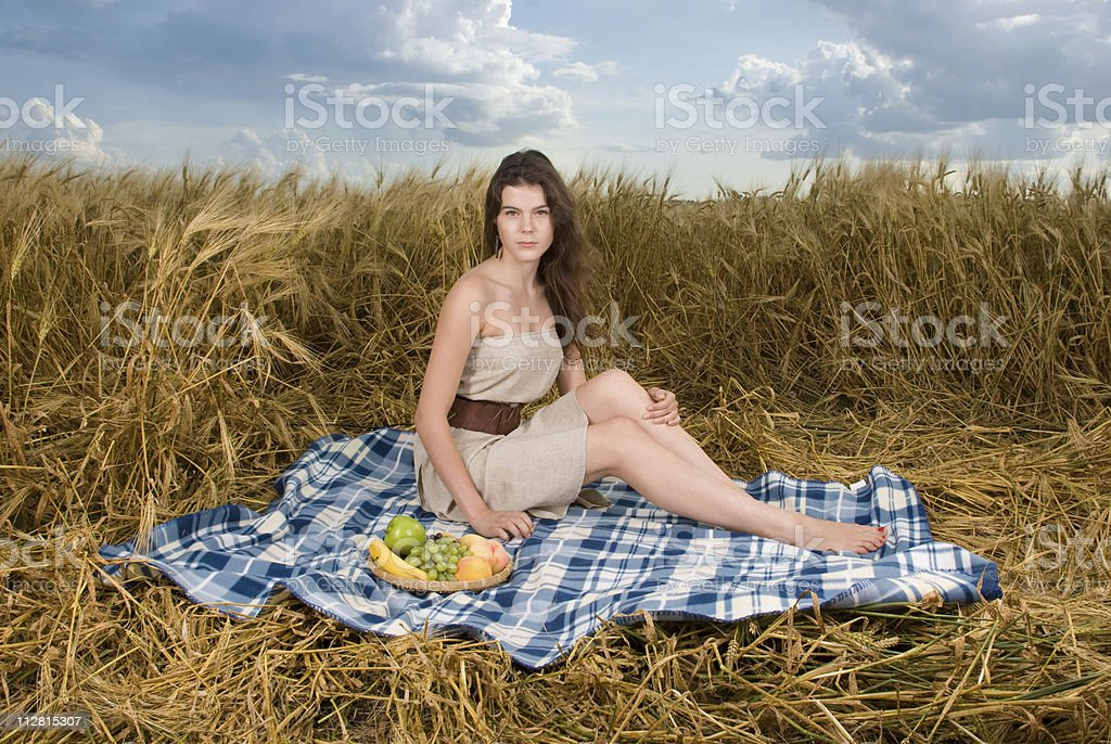 Beautiful slavonic girl on picnic in wheat field royalty-free stock photo
