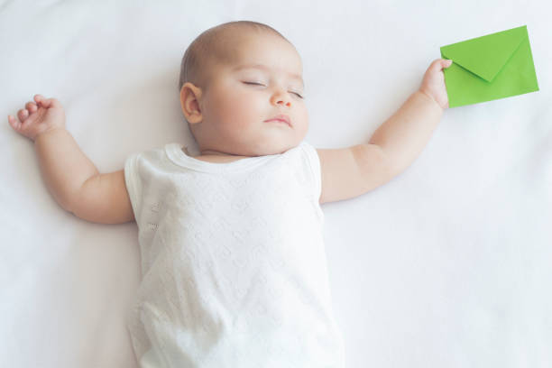 Beautiful Sleeping Baby is Holding Green Envelope stock photo