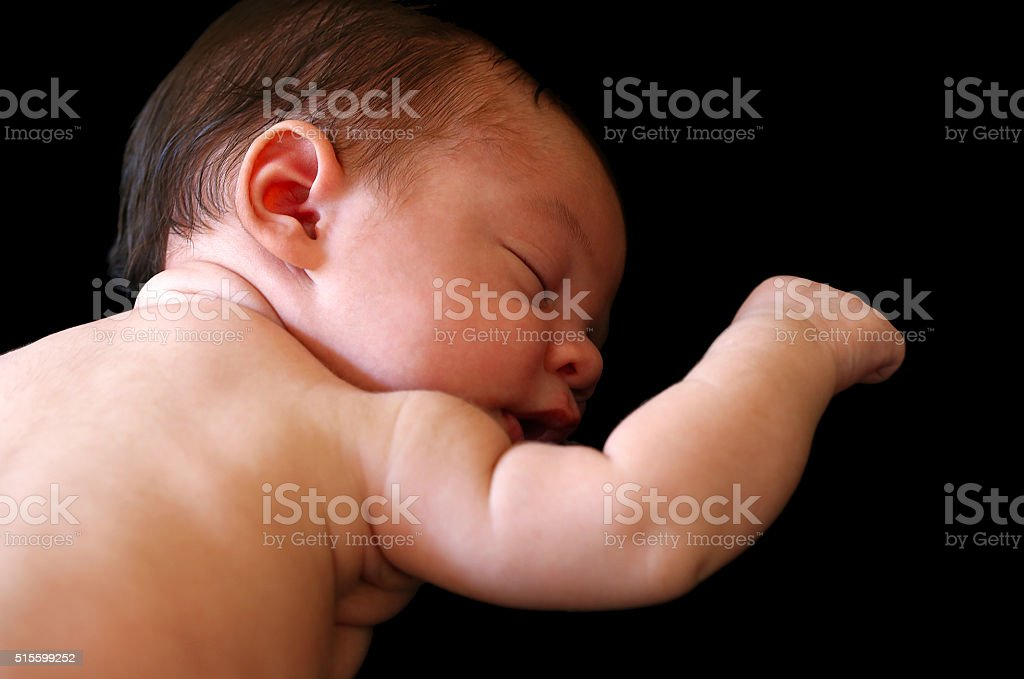 Beautiful sleeping baby with right hand raised on black background stock photo