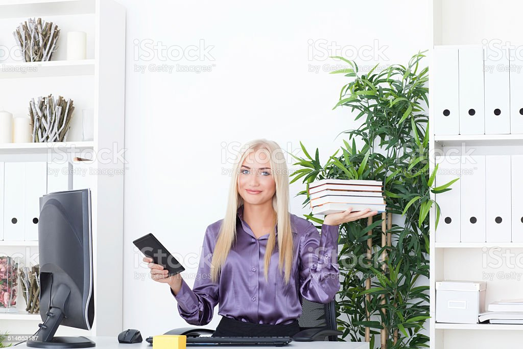 Beautiful, slender blonde compares a tablet and books at office stock photo