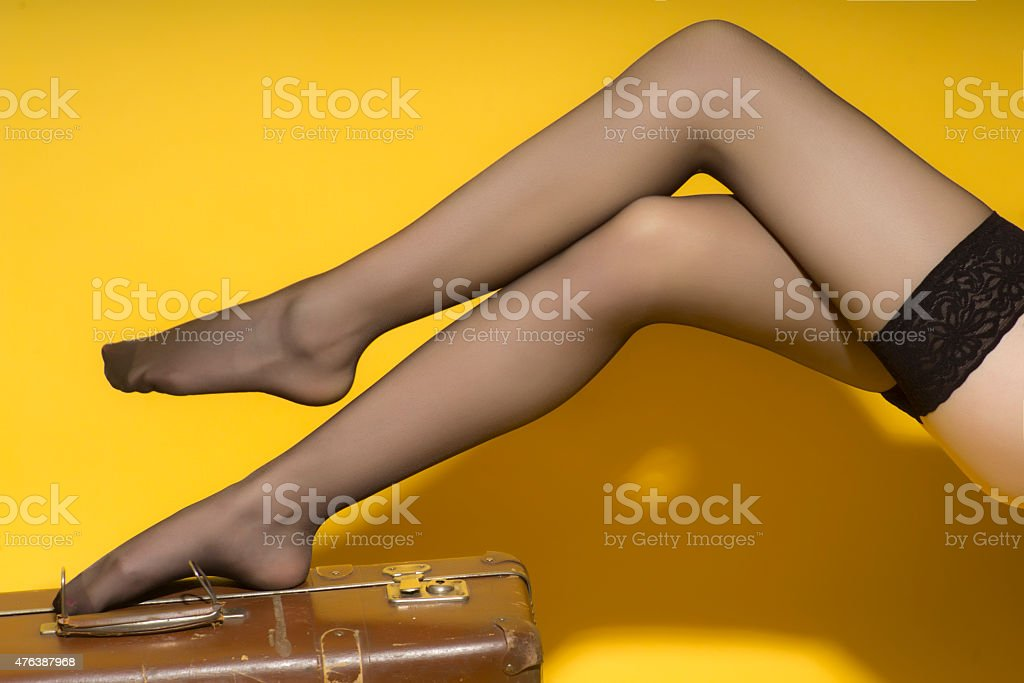 Beautiful slender female legs and suitcase stock photo
