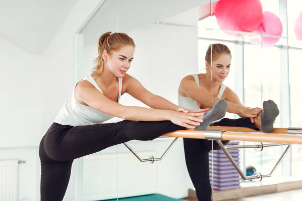 Beautiful slender woman in sportswear stretching near the ballet barre. stock photo