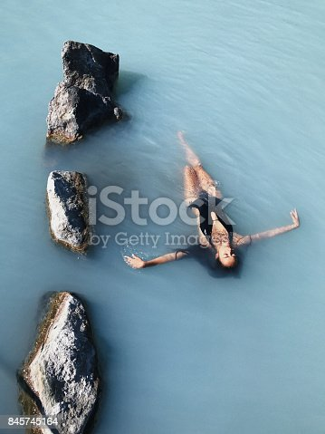 Beautiful slim girl with long black hair relaxing in Blue Lagoon Thermal Bath in Iceland. Natural spa treatment