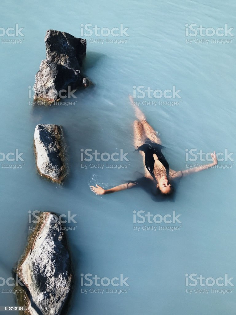 Beautiful slim girl with long black hair relaxing in Blue Lagoon Thermal Bath in Iceland. Natural spa treatment stock photo