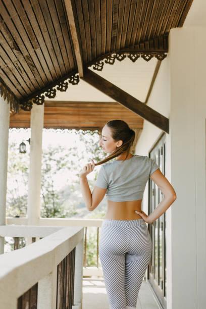 beautiful slim sportswoman in yoga pants standing on porch stock photo