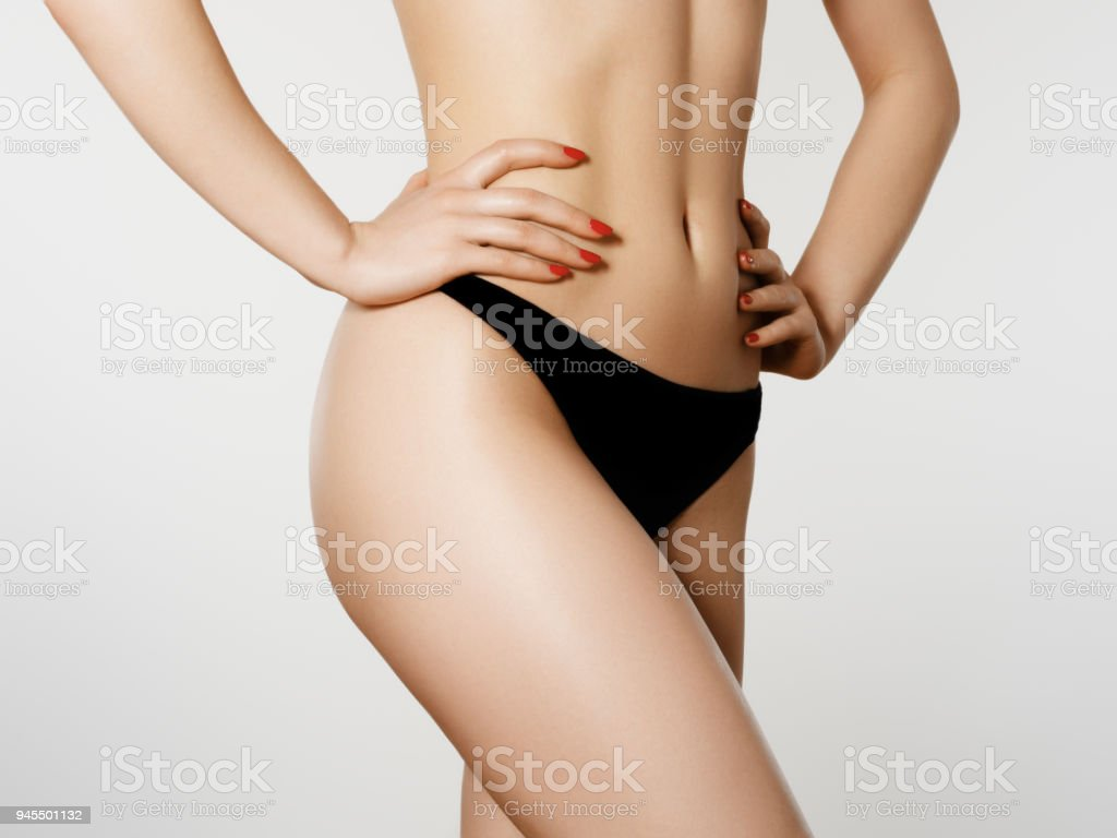 Beautiful slim woman's body. Perfect slim toned young body of the girl. Fitness or plastic surgery and aesthetic cosmetology. Firm buttocks. Sporty girl in black bikini posing on grey background стоковое фото