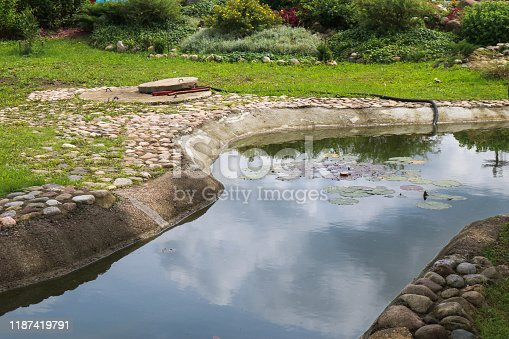 Beautiful small small pond stone natural homemade in nature. Landscaping with artificial pond.